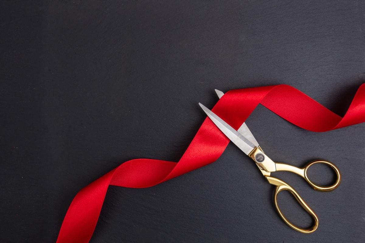 Schere zerschneidet ein rotes Band