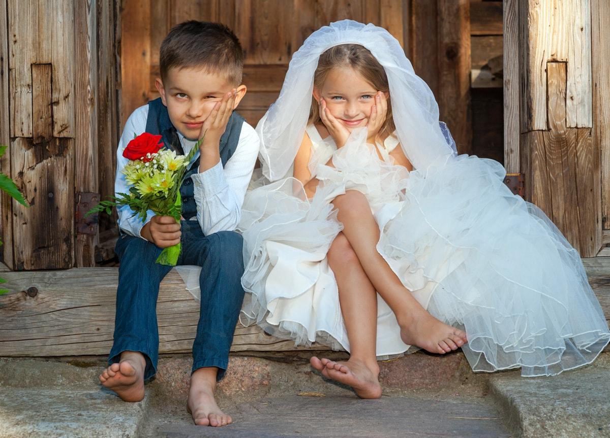 Kinder, Junge und Mädchen sitzen in Hochzeitssachen auf der Treppe